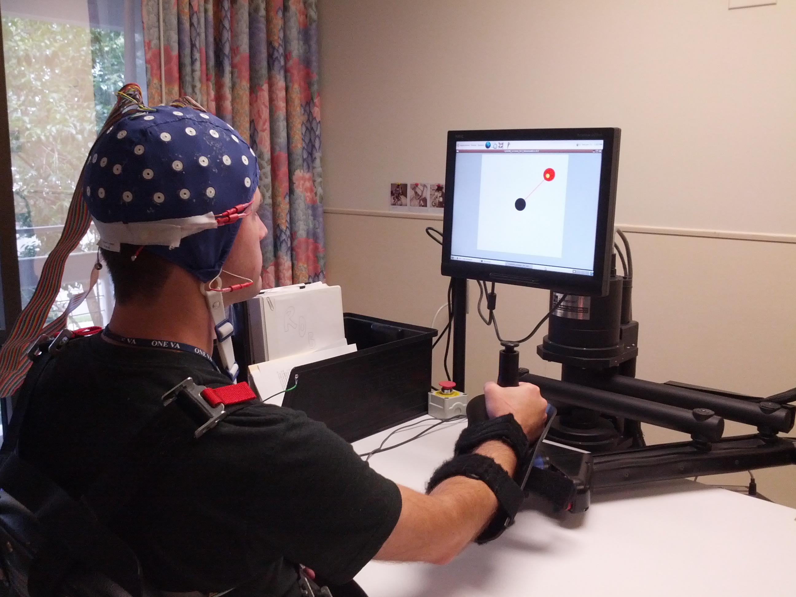 Research subject with EEG cap and therapy robot